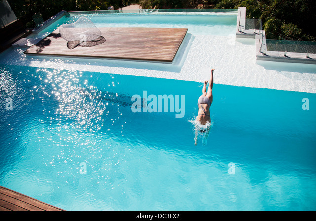 Woman diving in luxury swimming pool - Stock Image