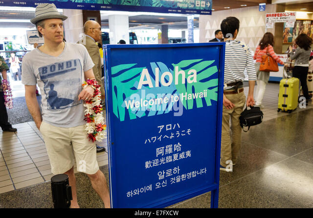 Hawaii Hawaiian Honolulu International Airport HNL sign Aloha welcome Japanese Chinese Korean multi languages man - Stock Image