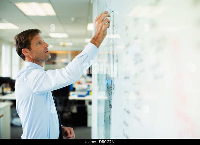 Businessman writing on whiteboard in office - Stock Image