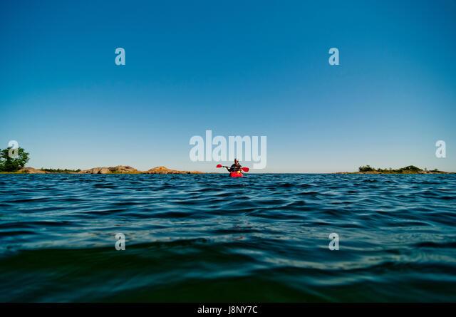 Man paddling in sea at sunset - Stock-Bilder