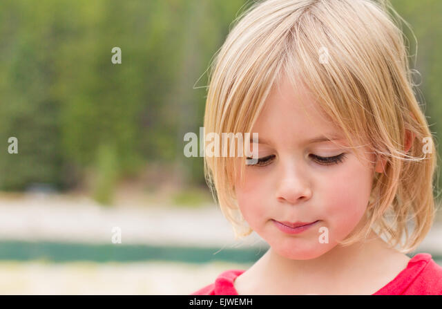 Timid Little Girl Looking Down with a Shy Look - Stock Image