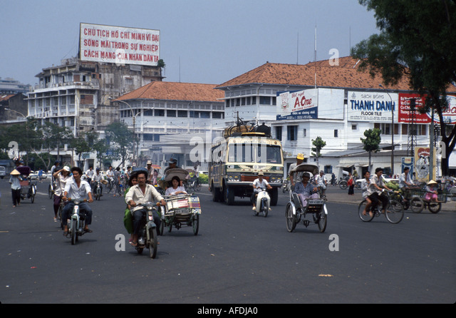 Vietnam Saigon Ho Chi Minh City Ben Thanh Circle traffic bicycles motor scooters businesses - Stock Image