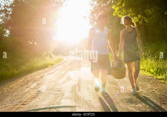 Full length front view of couple walking on dirt road against bright sun - Stock Image