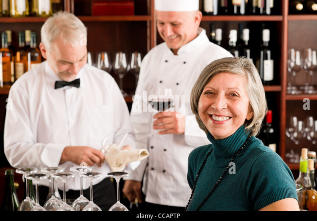 Restaurant manager smiling with staff at wine bar - Stock Image
