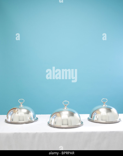 three silver serving dishes on table - Stock Image