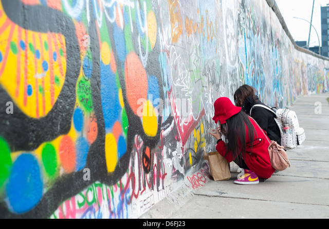 Asian tourists writing on the Berlin Wall at the Eastside Gallery - Stock-Bilder