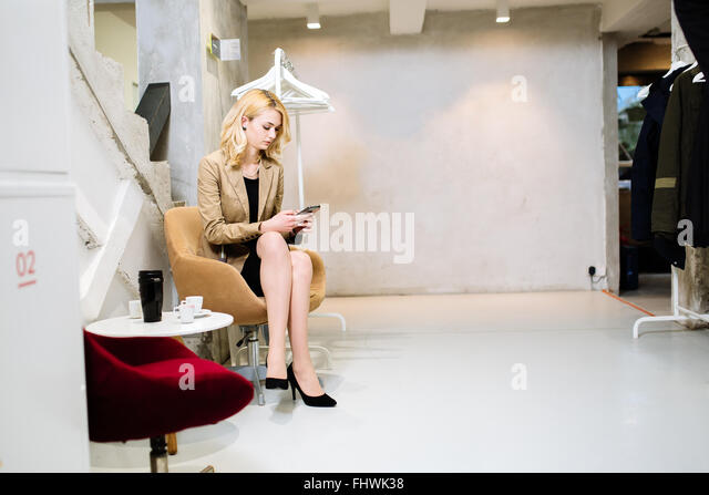 Businesswoman having break in corridor and using phone - Stock Image