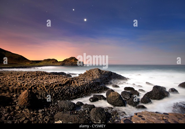 The Giants Causeway at night showing conjunction of Venus and Jupiter in sky. - Stock-Bilder