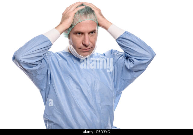 Depressed surgeon in theater garb or scrubs holding his hands to his head with a grim expression isolated on white - Stock Image