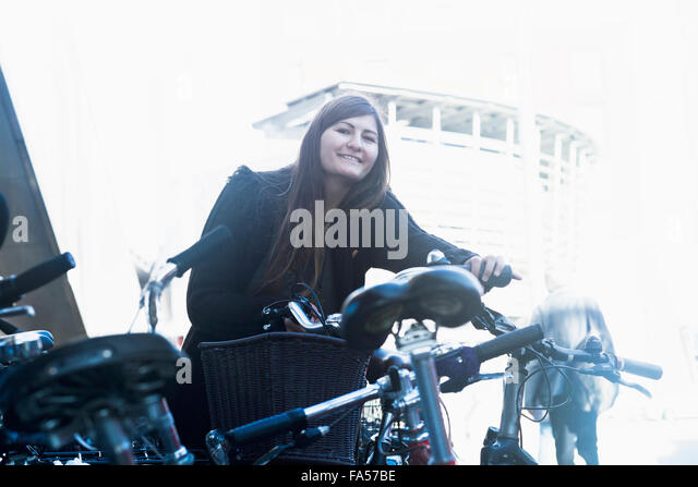 Young woman standing with bicycle in parking lot, Freiburg im Breisgau, Baden-Württemberg, Germany - Stock Image