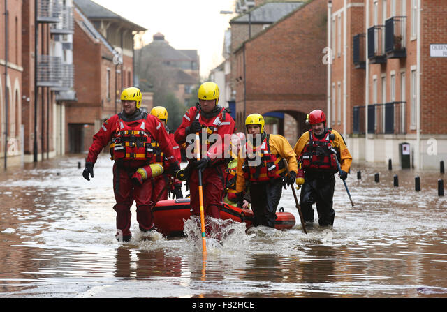 Rescue workers wade through high flood water in York, Yorkshire, UK, after both the River Ouse and Foss burst their - Stock Image