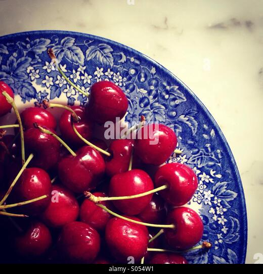 Red cherries in blue bowl. - Stock Image