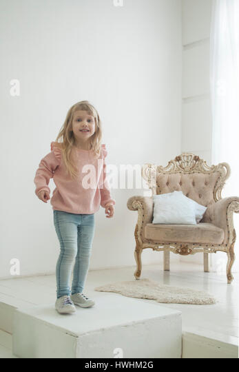 Little modern princess in jeans near her throne, white background - Stock Image