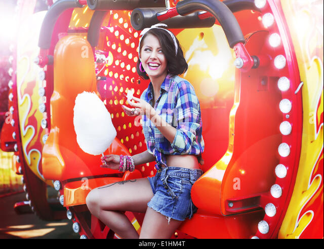 Lifestyle. Young Happy Woman Eating Sweetened Cotton Candy in Funfair - Stock Image