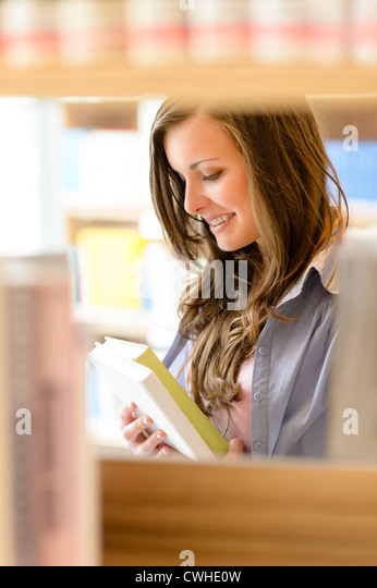 Young student woman reading book among library shelves - Stock-Bilder