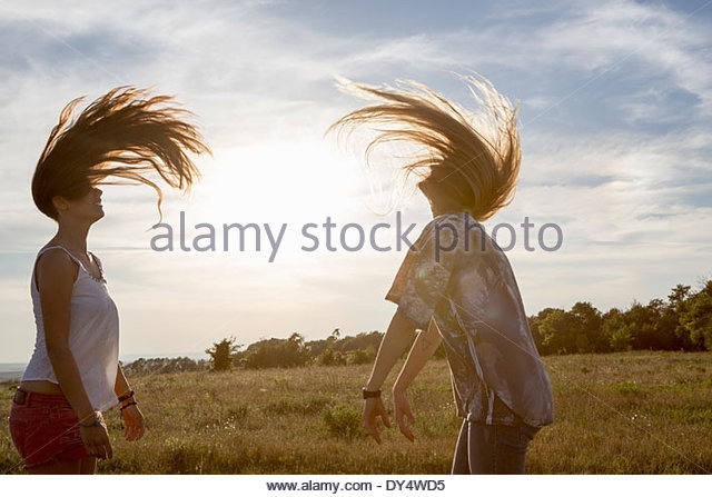 Two young women tossing long hair - Stock Image