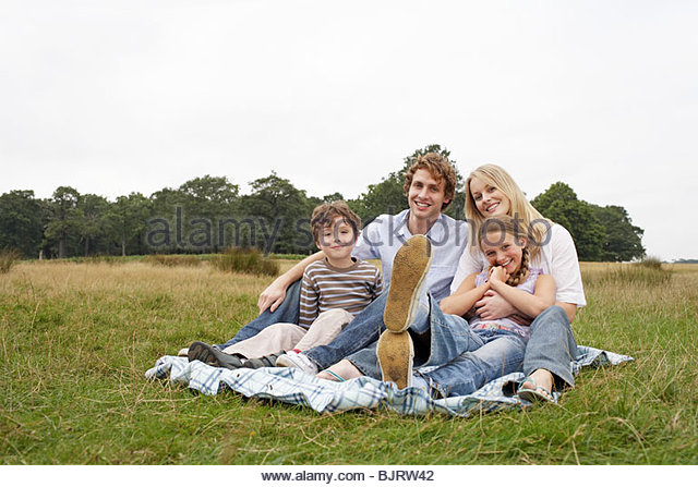 Family sitting in a field - Stock Image