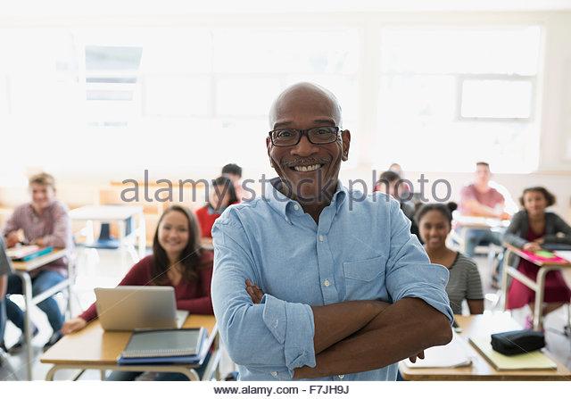 Portrait confident high school teacher with students classroom - Stock Image
