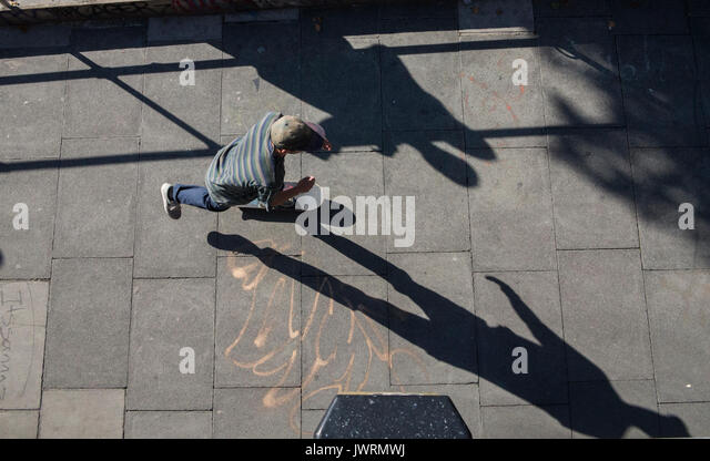 Long shadows of a skateboarder, taken from above as he commutes home - Stock Image