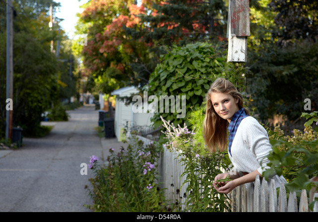 Teen with green bean harvest in urban garden - Stock Image