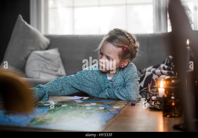 Sweden, Girl (4-5) playing board game on coffee table - Stock Image