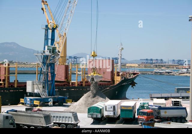 Trucks, Cranes, and Ships , Shipment of salt at Cagliari Harbour, Sardinia, Cagliari Port Sardinia truck lorry harbour - Stock Image