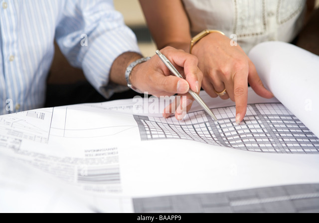 The hands of persons over a drawing in an office, Sweden. - Stock Image
