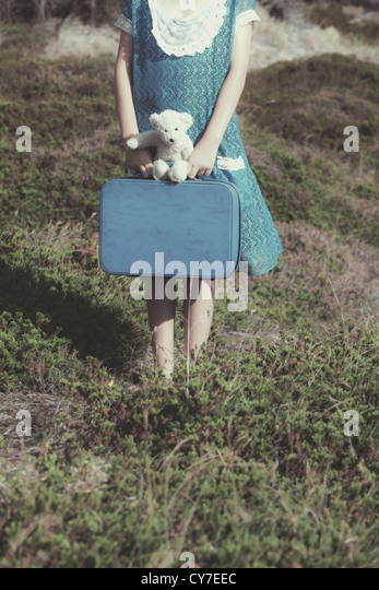 a young girl with a suitcase and a teddy bear - Stock Image