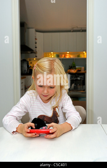 Little girl playing on the smart phone at home - Stock Image