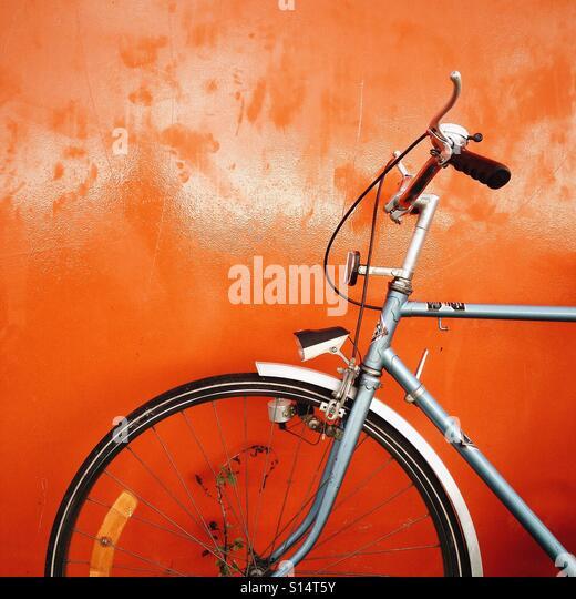 Bicycle on orange wall - Stock-Bilder