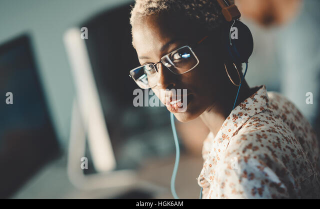 African american woman wearing glasses working on desktop in office - Stock Image