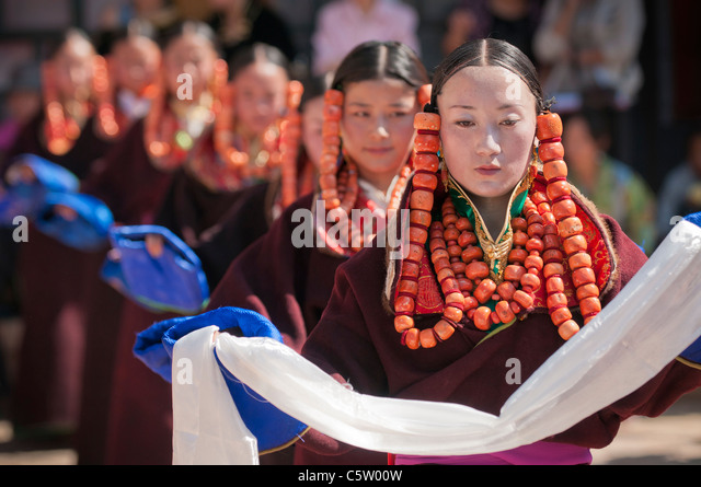 Young girls wearing heavy coral jewelry perform at shaman harvest festival, Tongren, Qinghai Province, China - Stock-Bilder