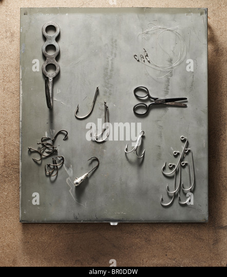fish hooks and scissors laid on a distressed, grey metallic background - Stock Image