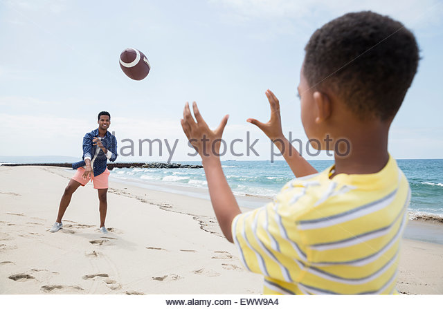 Father and son throwing football on beach - Stock Image