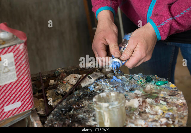 Artist squeezing a paint tube, Bavaria, Germany - Stock-Bilder