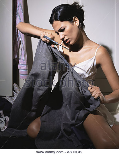 Woman cutting up mans clothes - Stock Image