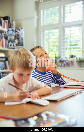 Boys working in home office - Stock Image