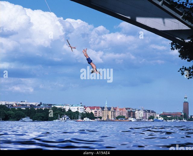 young man diving from bridge in Stockholm - Stock Image