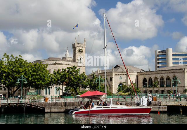 Marina with red sailboat and Parliament Buildings in background Bridgetown Barbados. - Stock Image