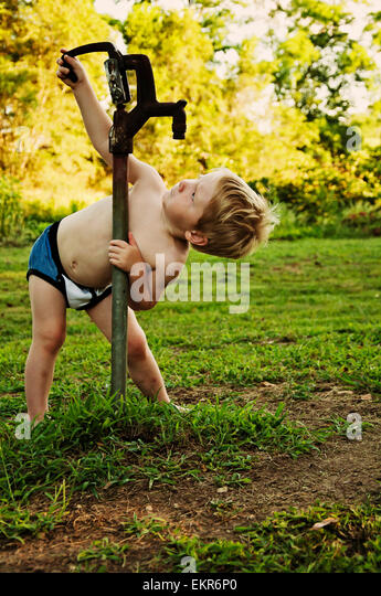 Boy looks for water in dry water pump - Stock Image