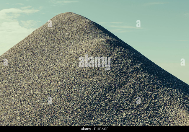 A large gravel pile, material used for construction and maintaining roads. - Stock Image