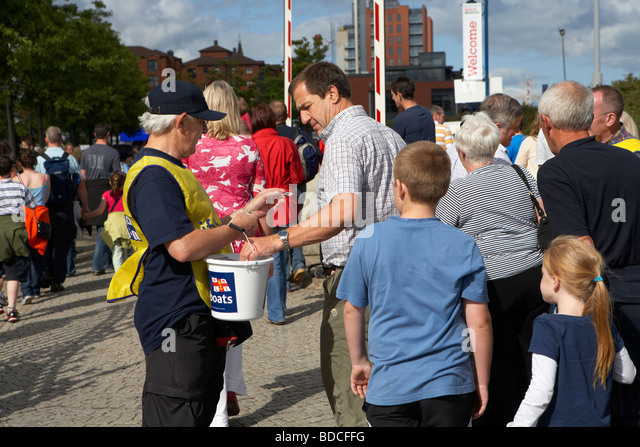 volunteer making a charity bucket collection for the RNLI at a busy outdoor event in Belfast northern ireland uk - Stock Image