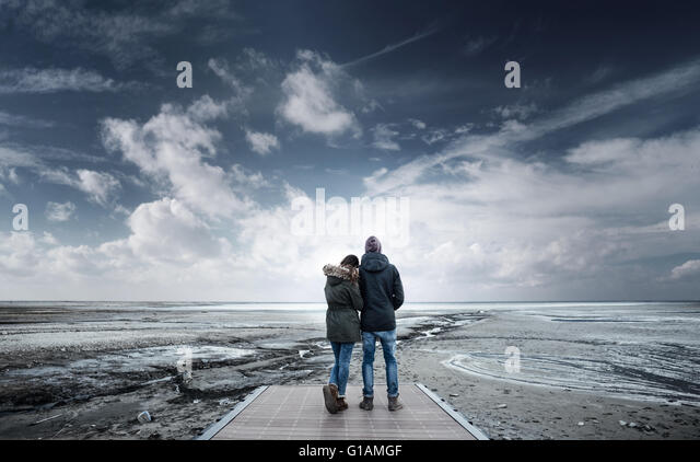 Romantic young couple on a pier looking away, back view, lake and mountains on background - Stock-Bilder