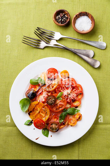 Ripe fresh colorful tomatoes salad with olive oil and balsamic vinegar on green background - Stock Image