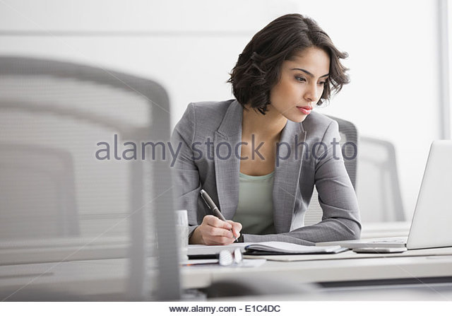 Businesswoman working at laptop in conference room - Stock-Bilder