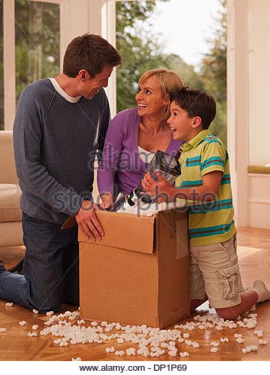 Family opening box in living room - Stock-Bilder