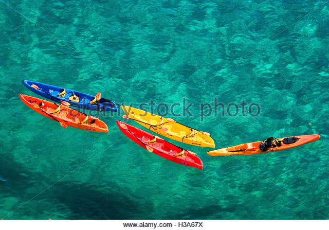 colorful kayaks in the ocean - Stock Image