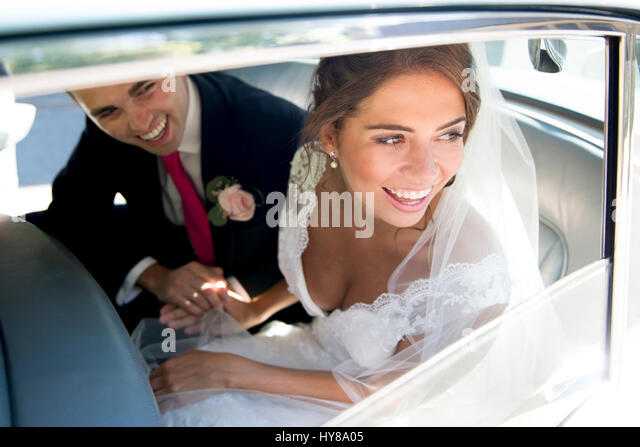 A bride and groom sit in the wedding car after getting married - Stock Image