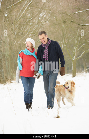 Senior Couple Walking Dog Through Snowy Woodland - Stock Image