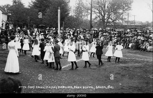 Full length landscape shot of schoolchildren doing hoop drill as a part of Mayday Exercises, girls wearing white - Stock Image